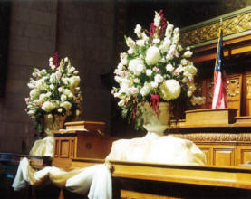 Large alter bouquets grace the assembly chamber